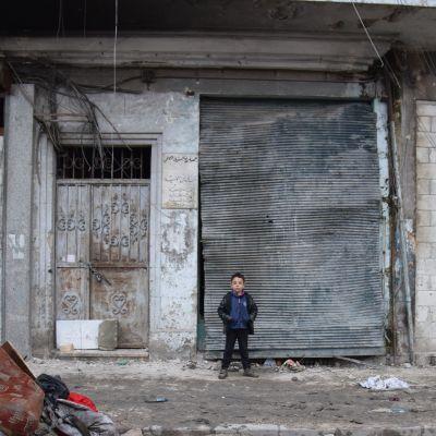 Lapsi sodasta kärsineen rakennuksen edessä.
