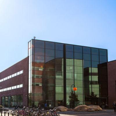 Bild på yrkesinstitutet Prakticums fasad, rött stenhus med stor glasvägg.