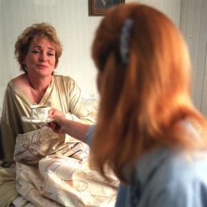 Leena Uotila (kameraan selin) ojentaa kahvikuppia sängyssään juuri heräävälle Rea Mauraselle.