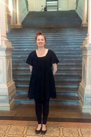 Konstnären och kuratorn Katriina Rosavaara står framför trappan som leder upp till Ateneums salar.