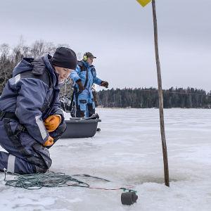 Fiskaren Tanja Åkerfelt och hennes pappa på isen fiskar med nät genom vaken på vintern.