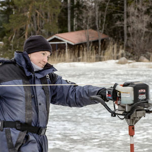 Fiskaren Tanja Åkerfelt drar igång isborren på vintern ute på isen en bit från stranden.