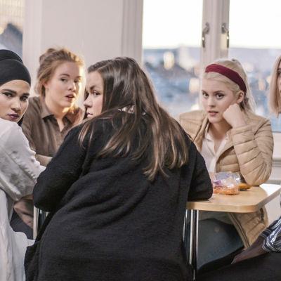 De fem huvudpersonerna i Skam som sitter kring ett bord.