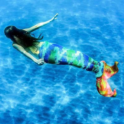 En sjöjungfru vars nedre del är stickad simmar i klarblått vatten.