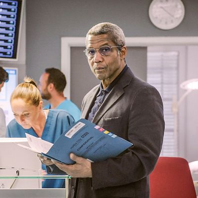 Mies seisoo sairaalassa kädessään aukioleva kansio ja katsoo kameraan