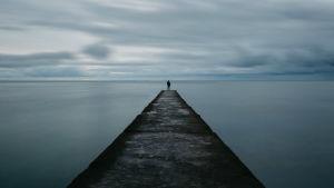 En person på en lång brygga tittar mot horisonten.