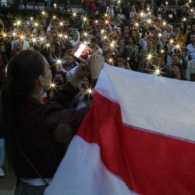 Mielenosoittajat pitävät Valko-Venäjän historiallista lippua ja pitävät kännyköiden valoja ilmassa Minskissä.