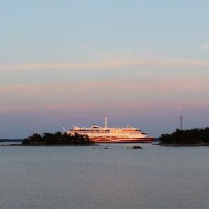 De sista solstrålarna lyser på Viking Grace en sen sommarnatt i skärgården, med lila-gul-blå himmel.