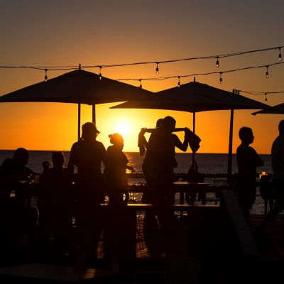 Ihmisiä terassilla auringonlaskun aikaan.
