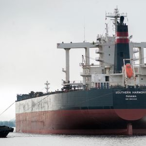 En lotsbåt drar ett stort fraktfartyg med tre linor.
