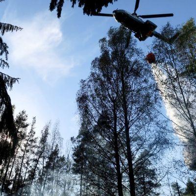 Rajavartiolaitoksen helikopteri auttamassa sammutustöissä pudottamalla 2000 litran sammutuspussilla vettä maastoon Nurmijärvellä 17. toukokuuta.