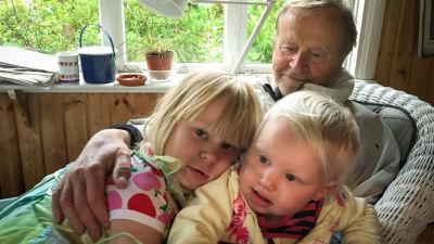 En äldre man sitter med två små barn i famnen.