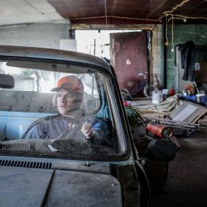 Näyttelijä Juho Uusitalo istuu autonromun ratissa sekaisessa autotallissa ja tuijottaa vakavana eteensä