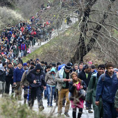 Tuhansia pakolaisia kävelee kreikkalaisen Idomenin kylän leiriltä kohti Makedonian rajaa 14. maaliskuuta.