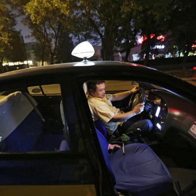 Taksikuljettaja istuu autossaan ja katsoo älypuhelintaan.
