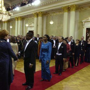 Diplomaterna anländer. President Tarja Halonen möter dem. Året är 2000.