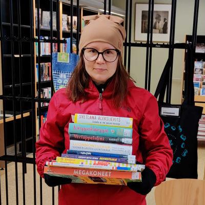 En kvinna står med en hög böcker i famnen inne i ett bibliotek.