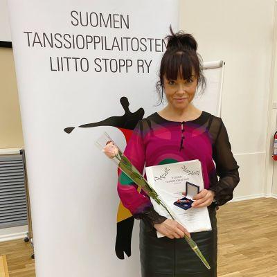 Katja Köngäs står och håller i en blomma, ett diplom och en liten ask.