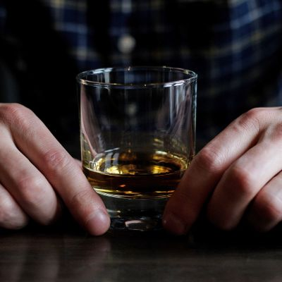 miehen kädet ja viskilasi