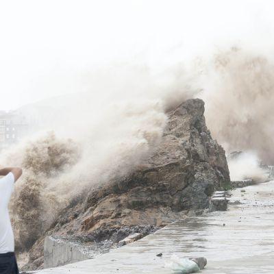 Mies valokuvasi myrskyaaltoja Wenlingin kaupungin läheisyydessä Kiinassa 10. heinäkuuta.