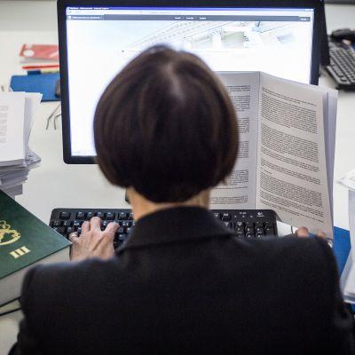 Nainen päätteen ääressä lakikirjoja ja papereita ympärillään.