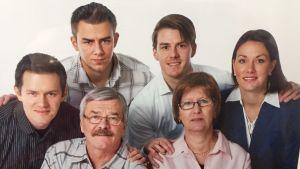 Perhepotretti, jossa äiti, isä, kolme poikaa ja yksi tytär hymyilevät kameralle.