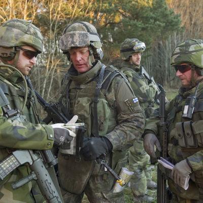 Fyra män i militärkläder. Tre av dem tittar på något som en av dem håller i sin hand. Den fjärde mannen står bakom dem. Den man som håller i något i sin hand har ett gevär över sin axel. Alla har typiska kamoflagekläder.