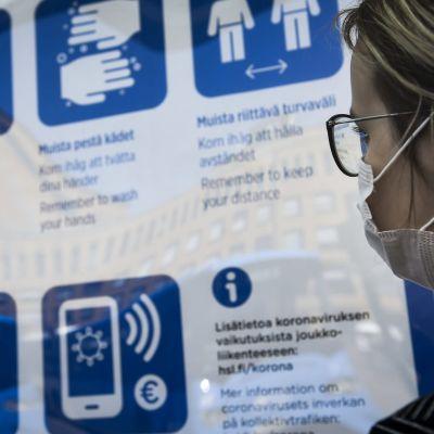 Hengityssuojainta käyttävä nainen katsoi turvallisuusohjeita bussipysäkillä Helsingissä kesäkuussa.