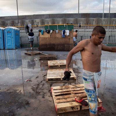 Siirtolaiset rämpivät mutavellissä Tjuanaan pystytetyssä väliaikaissuojassa.