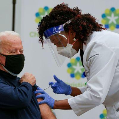 Joe Biden, iförd en ett svart munskydd, blir vaccinerad av skötare med munskydd och visir.