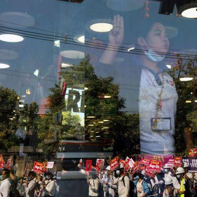 Kauppatyöntekijä tervehti liikeen ohi liikkuvia protestoija osoittakseen tukea sotilasvallankaappausta vastustavalle mielenosoitukselle.