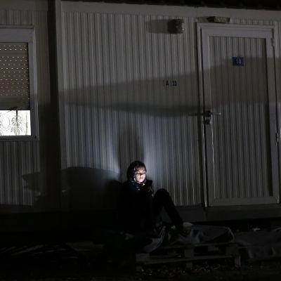 Nainen istuu puhelimensa valossa Ateenan Elaionasin kaupunginosaan perustetussa väliaikaisessa pakolaiskeskuksessa 2. syyskuuta.