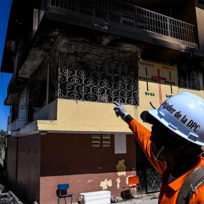Palomies osoittaa orpokotia, jossa syttyi tuhoisa tulipalo torstai-iltana.