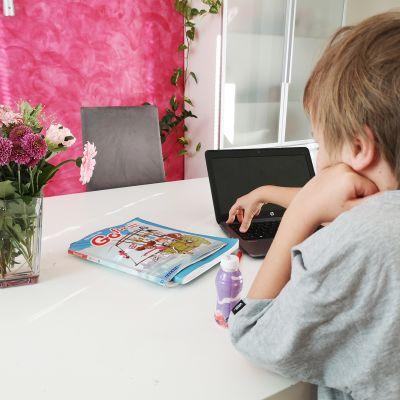 lapsi kotona kirjojen ääressä