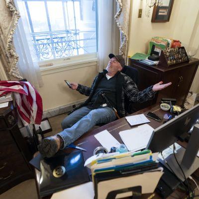 Donald Trumpin kannattaja poseerasi edustajainhuoneen puhemies, demokraatti Nancy Pelosin työpöydällä sen jälkeen, kun protestoijat olivat onnistuneet tunkeutumaan sissän kongressirakennukseen.
