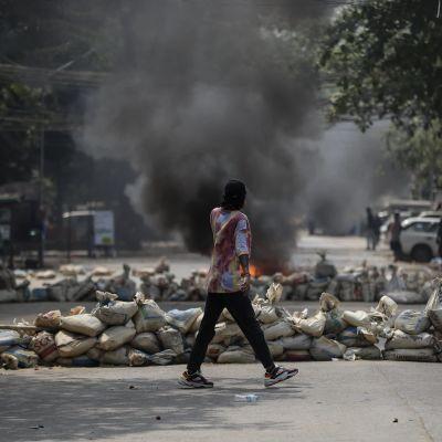 Mielensosoittaja käveli savuavien barrikadien keskellä Yangonissa toissapäivänä.