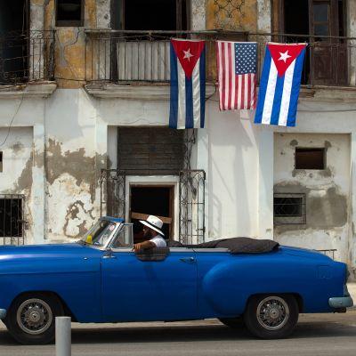 Vanha auto ohittaa taloa jossa roikkuu Yhdysvaltain ja Kuuban lippuja.