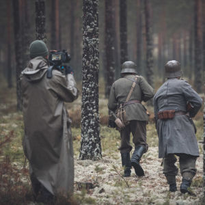 Inspelning i skog, soldater (skådespelare) springer med ryggen vänd mot kameran mellan tallar. De har hjälmar och gevär.