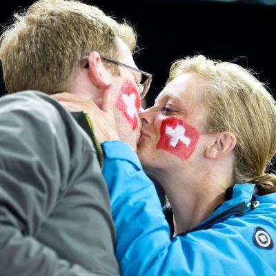 Sveitsiläiset jääkiekkofanit suutelevat katsomossa.