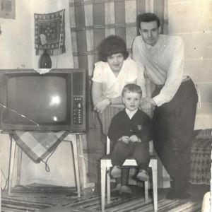 Vanha perhevalokuva 1960-luvulta: äiti, isä ja pikkupoika poseeraavat tv-vastaanottimen ääressä.