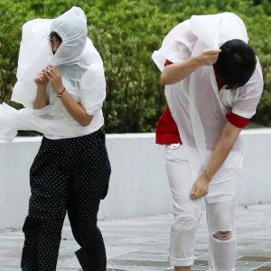 Folk stretar fram i Osaka i den hårda vinden.