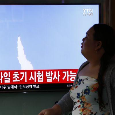 Televisioruutu, jossa näkyy ilmassa lentävän ohjuksen vana. Kuvan alareunassa on koreankielistä tekstiä. Televisioruudun oikealla puolella istuu nainen, joka katsoo kohti televisiota.