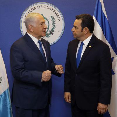 Morales keskustelee Netanjahun pariskunnan kanssa Guatemalan ja Israelin lippujen edessä.