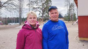 En kvinna och en man står ute på en gård. De tittar in i kameran.