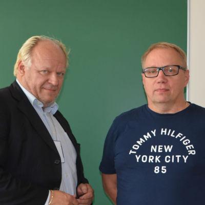 Två män står framför grön vägg.