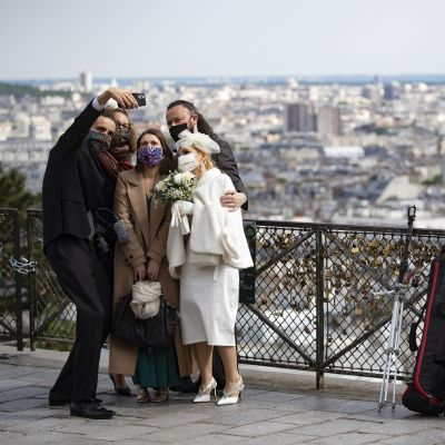 Hääpari ja kolme muuta ihmistä vieri vieressä ottamassa selfietä ulkona.