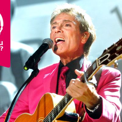 Cliff Richard spelar akustisk gitarr och sjunger i en mikrofon.