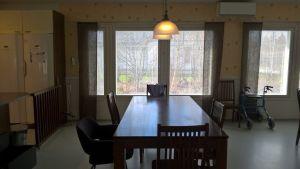 Ett mörkt matbord vid ett fönster.