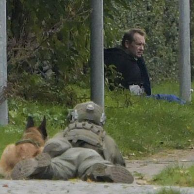 Bild från Albertslund, väster om Köpenhamn, visar Madsen i gräset omgiven av polisens specialstyrkor.