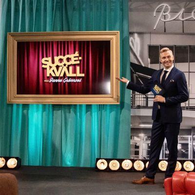"""Janne Grönroos står på en scen och pekar på en tavla där det står """"Succékväll""""."""